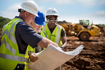 Duke Energy engineers look over plans at a coal ash site.