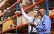 Two managers reviewing warehouse contents