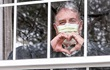 Photo of man wearing a mask making a heart sign as he looks out a window.
