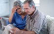 couple looking concerned while opening bills