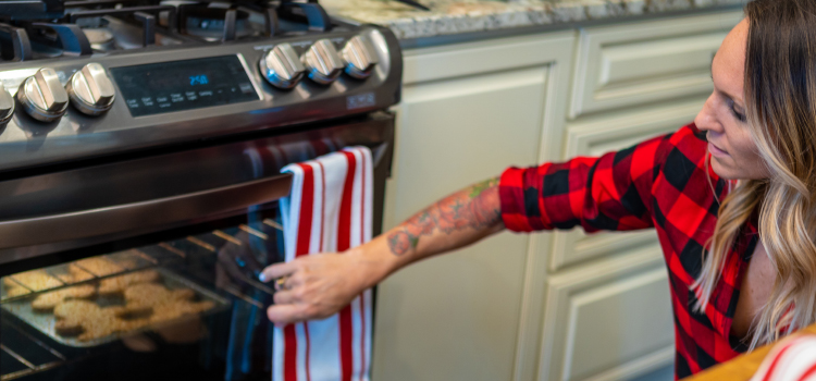 A woman looking into an oven with cookies baking