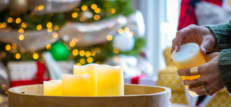 Candles on a table with Christmas décor in the background