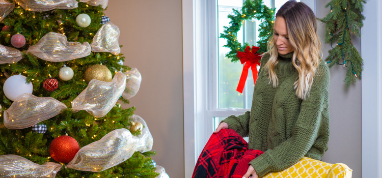 Christmas décor and a lady standing next to a yellow chair with a red blanket in her hand